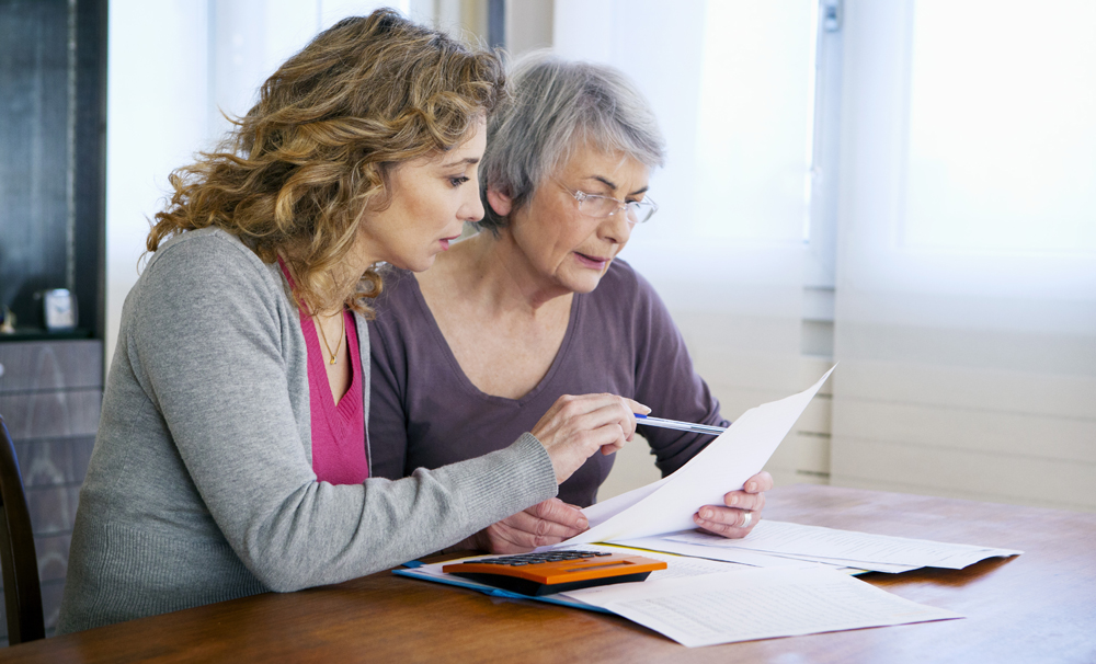 patient advocate helping elderly parent review medical bill