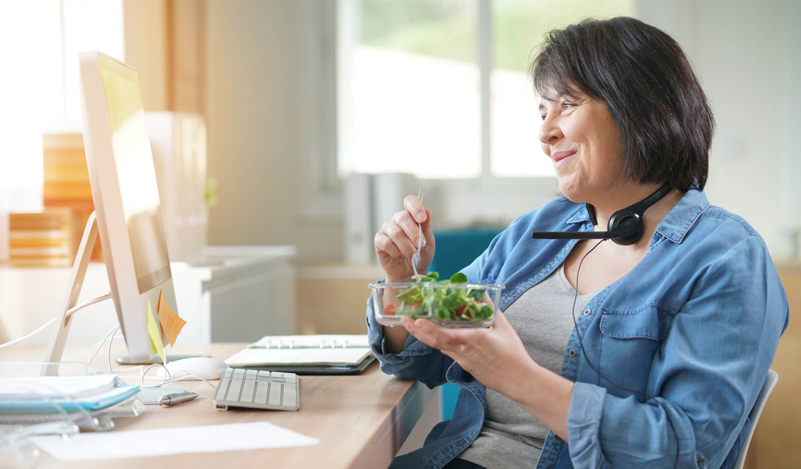 Woman eats a healthy lunch while chatting online with her weight-loss coach
