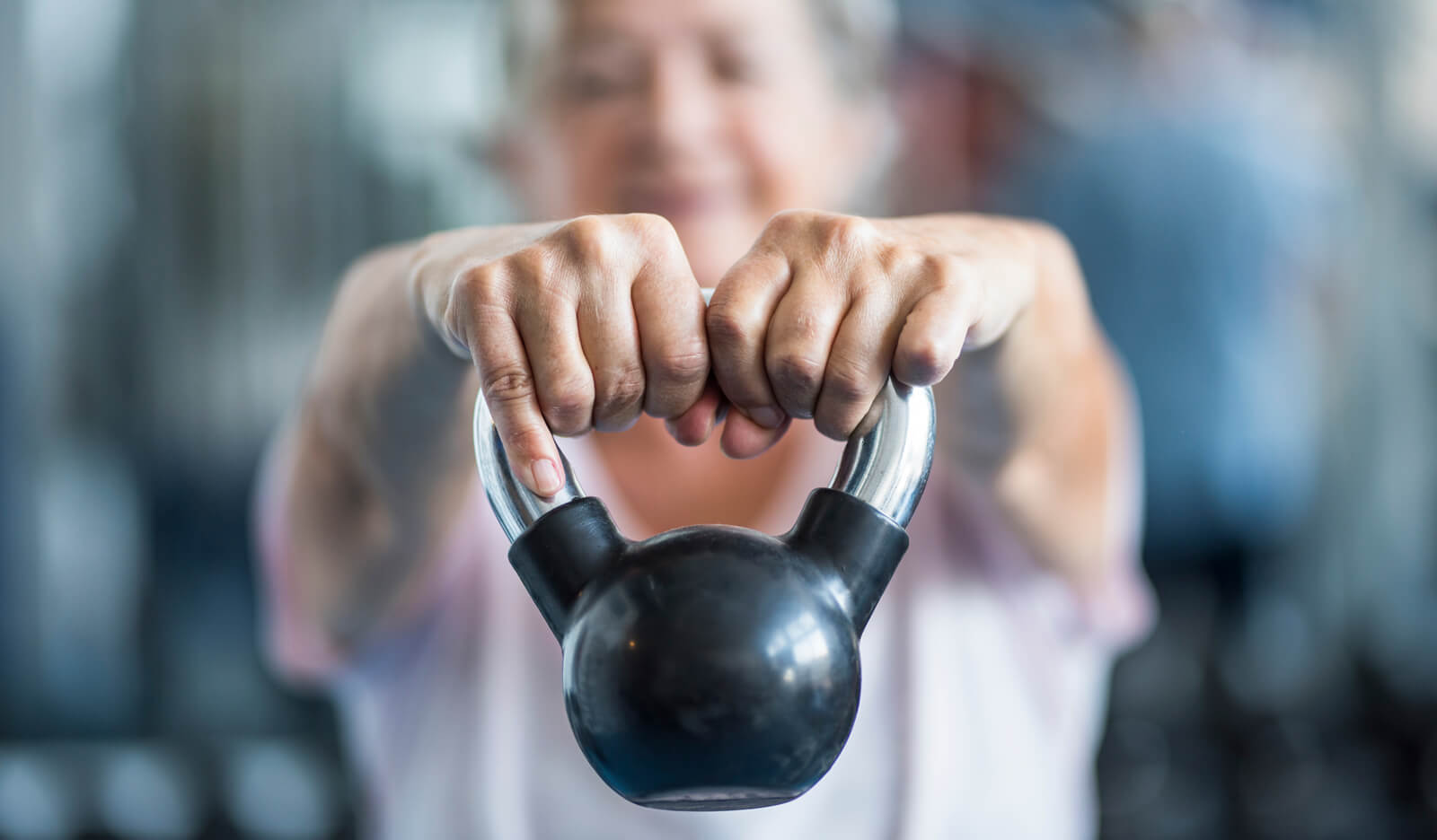Woman does strength training with a kettle ball