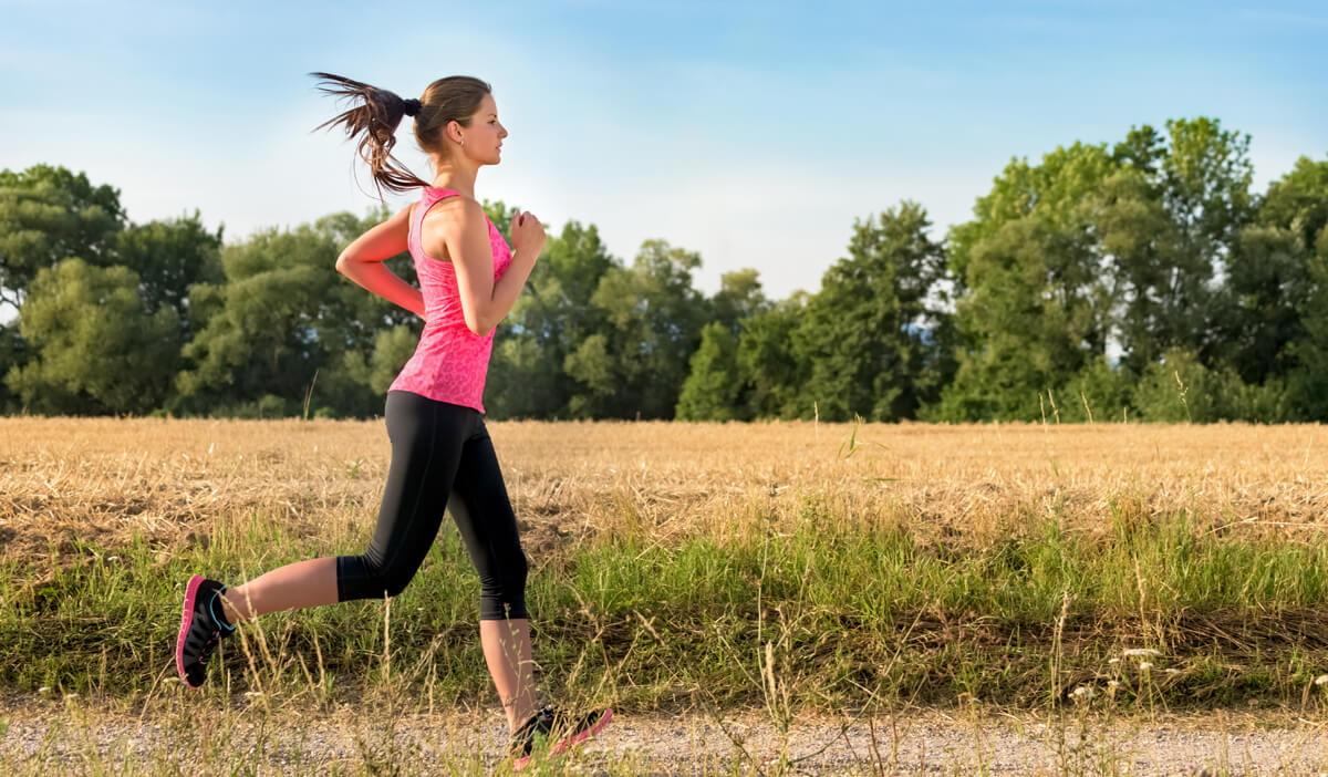 woman—who is jogging near farmland—wears proper footwear to avoid common running injuries