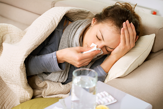 Woman sick with a head cold
