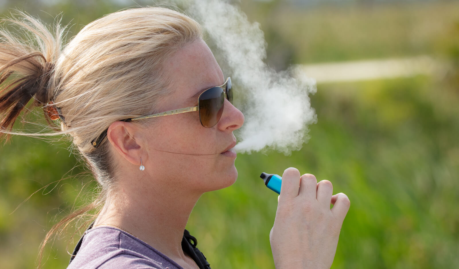A woman vapes using an e-cigarette